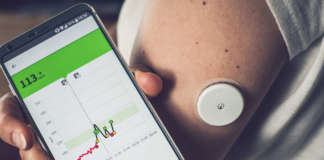 Woman checking glucose level with a remote sensor and mobile phone, sensor checkup glucose levels without blood. Diabetes treatment.